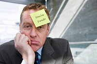 Businessman with ´you´re fired´ note attached to his forehead