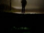 Person standing on road person går på väg i dimma på hösten eller vintern efter mörkrets inbrott