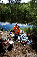 Two boys sitting on rock at river bank Lunch på utflyktsön i sjön.