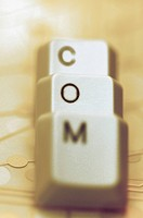 Close_up of three computer keys spelling the word COM