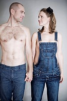 Close_up of young couple holding hands, studio shot