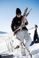 Front view of man carrying log in hands by snowcapped landscape En ung man i solglasögon bär ved på en sluttning i fjällen.