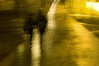 Silhouette Of Two Women Walking In The Park On A Rainy Night