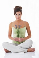 A woman sitting crossed legged holding lavender