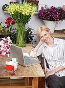Female florist with laptop portrait