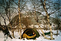 Man in tent by snowcapped mountain 712007