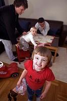 Skrattande Flicka, 4 År, I Röd Tröja I Bakgrunden Sitter Mamma, Pappa Och Lillasyster I Soffan , Portrait Of Girl 3_4 Smiling