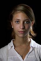 Close_up of woman, portrait flicka med neutral blick som tittar in i kameran mot svart bakgrund