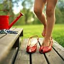 Girl wearing shoe on wooden steps, low section Ett barn provar ett par för stora röda damskor på en trätrapp med en röd vattenkanna och en hög halsban...