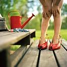 Girl standing with hand on knee, low section Ett barn står med fötterna i ett par för stora röda damskor med händerna på de nakna knäna och en röd vat...
