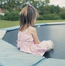 Girl 4_5 years sitting on trampoline in garden En liten flicka i blommig sommarklänning sitter på en studsmatta.