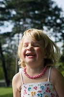 En Finkädd, 4_Årig Flicka I Blommig Klänning Som Skrattar , Close_Up Of Girl4_5 Years Laughing