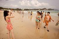 Badande Kinesiska Turister. Den Växande Medelklassen I Kina Har Råd Att Resa Bort Semestern., Woman Taking Photograph Of Couple On Beach