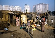 Fattigkvarter På Ödetomt I Mumbai Bombay Framför Nybyggda Hyreshus, People Sitting At Hut With Building In Background