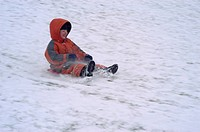 Fife year old boy sliding down a slope