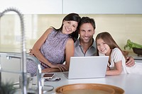 Family using laptop in kitchen