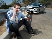 Man with crashed car calling for roadside assistance