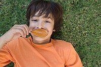 Boy holding leaf over mouth