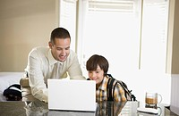 Father and son looking at laptop in kitchen