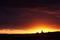 Sunset with dramatic sky at the southern point of africa with lighthouse: Cape Agulas (South Africa)