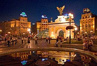 Ukraine Kiev Place of Independence people tourists visitors sit on the place with view to the Pecers´kyi gate with archangel Michael and fountain with...