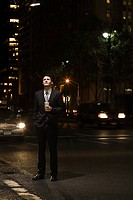 Businessman standing in a road at night