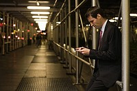 Businessman text messaging in a walkway