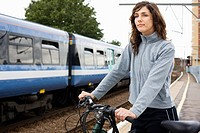 Woman with bike at train station