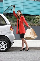 Woman by car with shopping bags