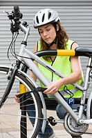 Woman locking bicycle