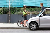 Woman with bicycle and man with car