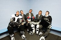 Exhausted businessmen after a game of ice hockey