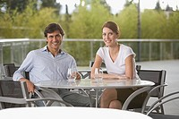 Smiling couple at dining table (thumbnail)