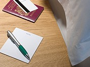 Passport and pen on bedside table