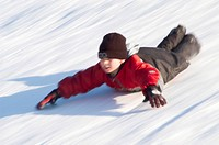 Boy sliding on his belly downhill