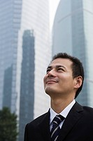 Grinning businessman looking up