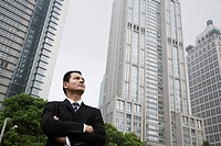 Serious looking businessman near skyscrapers