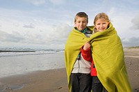 Children in blanket by the sea