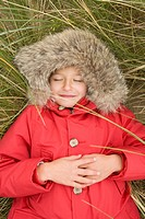 Girl lying on marram grass