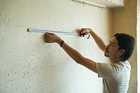Young man measuring wall