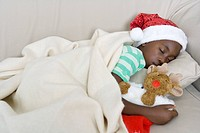 Girl sleeping on a couch with a Christmas hat holding a reindeer teddy.