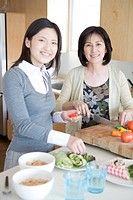 Portrait of mother and daughter in kitchen, smiling