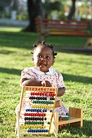 Daughter playing with her wooden abacus on the grass. Dewaal Park, Cape Town, Western Cape Province, South Africa