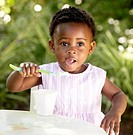 Baby girl eating yogurt outdoors. Cape Town, Western Cape Province, South Africa