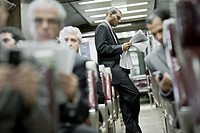 Commuter Standing on a Train Reading a Newspaper