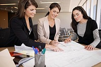 Three businesswomen examining blueprint