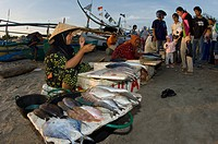 Women sell their catch on the beach at a fish market in Bali, Indonesia.