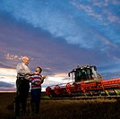 Farmer and grandson standing next to combine harvester in wheat field