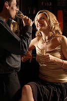 Mid adult couple drinking champagne at bar (thumbnail)