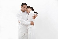 Woman and man in white clothes hugging